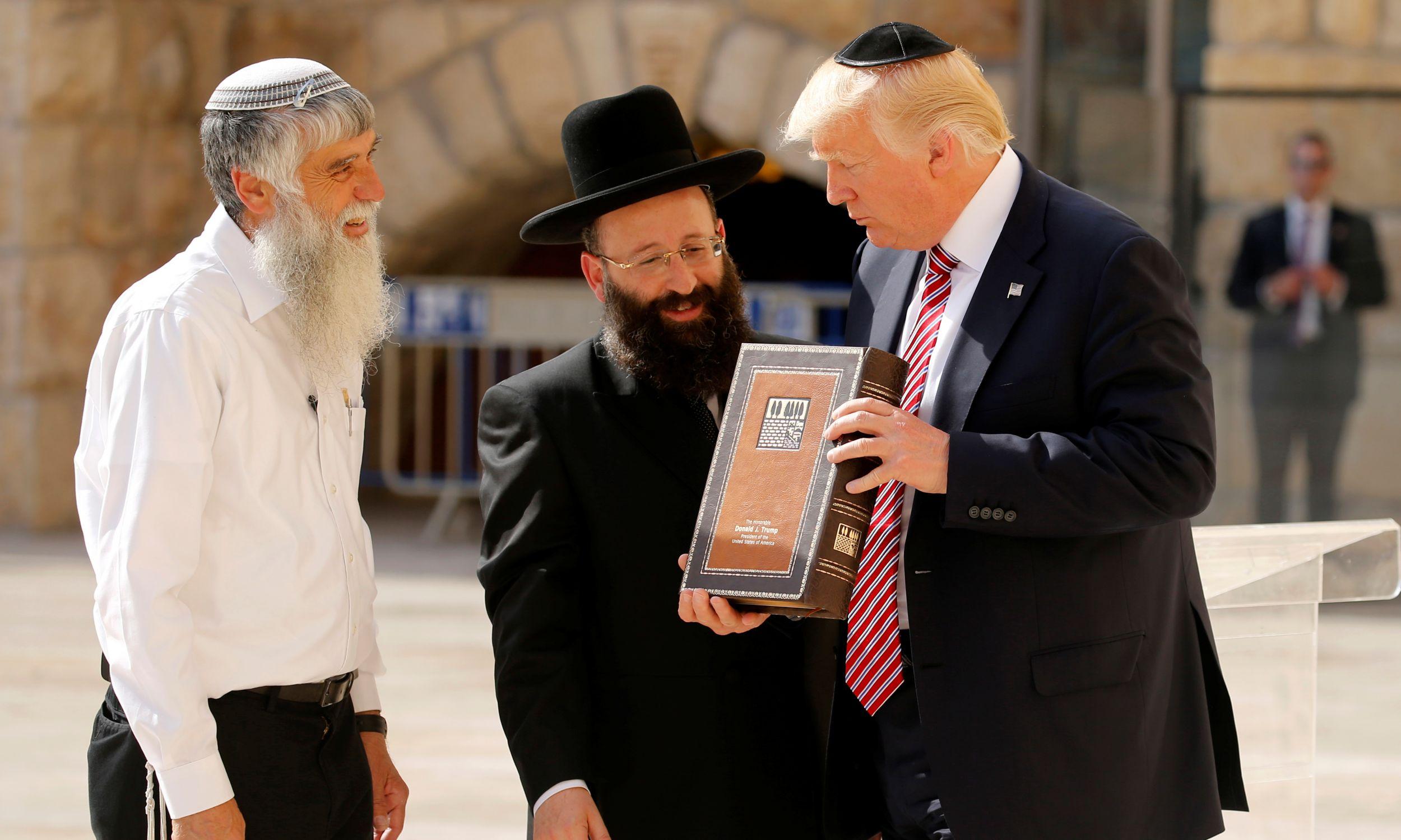 Prezydent USA Donald Trump (po prawej) otrzymuje w darze Księgę Psalmów od dyrektora generalnego Fundacji Ściany Płaczu Mordechaia Eliasa (po lewej) i rabina Ściany Płaczu Szmuela Rabinovitcha (w środku). Jerozolima, maj 2017. Fot. REUTERS/Jonathan Ernst