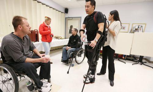"""Ale ma też umożliwić chodzenie osobom dotąd przykutym do wózków inwalidzkich. Tu Robert Woo demonstruje działanie """"egzoszkieletu"""" w 2012 roku w Mount Sinai Medical Center w Nowym Jorku. Jest architektem, który został sparaliżowany od bioder w dół podczas wypadku na budowie. Myślał, że już nigdy nie będzie chodził, tymczasem egzoszkielet wykorzystuje silniki i czujniki do fizycznego poruszania nogami. Fot. Scott Eells / Bloomberg via Getty Images Zdjęcie: Mario Tama / Getty Images"""