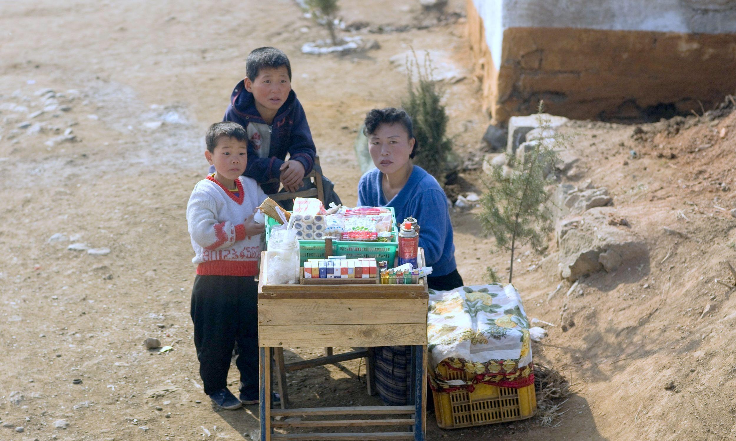 Nampo, Korea Północna. Kobieta z Korei Północnej z dziećmi sprzedają żywność i papierosy wzdłuż drogi na wsi, w południowej prowincji Phenianu. Fot. Eric Lafforgue / Art In All Of Us / Corbis via Getty Images