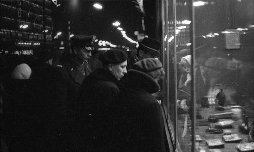 """Seria zdjęć do reportażu """"Godzina szczytu"""", w tygodniku """"Świat"""" nr 9 z 4 marca 1962. Na zdjęciu zatłoczone Aleje Jerozolimskie w Warszawie. Trwają zimowe wyprzedaże, tzw. biały tydzień. Przechodnie przed witryną sklepu """"Chinka"""", odcinek przed ulicą Kruczą, z lewej Centralny Dom Towarowy (""""Smyk""""). Fot. Muzeum Narodowe w Warszawie/PAP/Jan Kosidowski"""