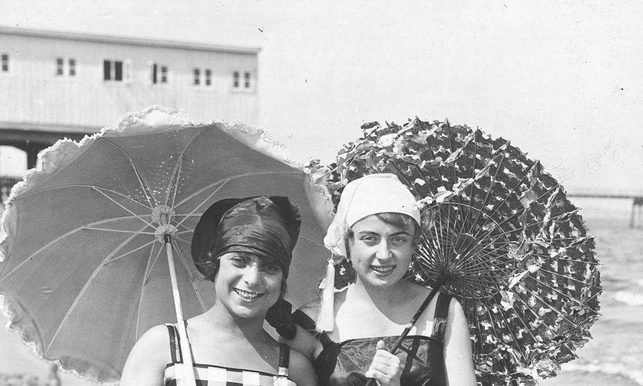 Już w latach 20. zaczęła panować moda na opalanie się. Dlatego też kostiumy ulegały ogromnej przemianie, skracały się i miały odkryte ramiona. Głowę chroniono, by nie dostać udaru a nie chronić się przed słońcem, najczęściej słomkowymi kapeluszami z dużym rondem. Zakładano także jedwabne chustki i apaszki. Niezbędnym przedmiotem na plaży były rzecz jasna parasolki, które chroniły od wiatru i udaru. Na zdjęciu kobiety spacerujące po plaży bałtyckiej. Lata 1918 – 1939. Fot NAC/IKC, sygn. 1-M-2943-9