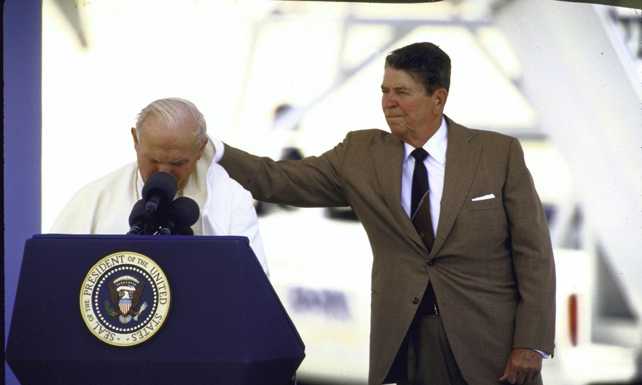 Jan Paweł II przemawia podczas swej pielgrzymki do USA w 1987 r., a prezydent Ronald W. Reagan łapie piuske, którą wiatr zwiał papieżowi z głowy,Fot. Dirck Halstead / The LIFE Images Collection via Getty Images / Getty Images)