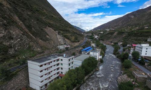 """""""Kopalnia bitcoinów"""" w budynku z niebieskim blaszanym dachem, obok elektrowni wodnej w Ngawa (Aba) – prefekturze autonomicznej tybetańskiej mniejszości etnicznej i mniejszości etnicznej Qi, 2016 r. Płaskowyż Tybetański to obszar obfitujący w energię wodną, co jest kluczowym czynnikiem wpływającym na opłacalność """"kopalń"""". Z powodu dużej liczby komputerów są one bowiem wysoce energochłonne. Energia elektryczna zazwyczaj stanowi 60-70 procent wydatków """"kopalni bitcoinów"""". Fot. PAP/EPA/LIU XINGZHE/CHINAFILE"""