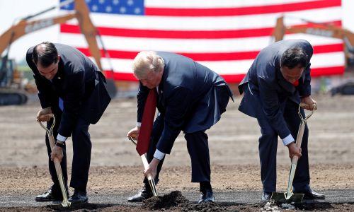 USA, 28 czerwca 2018 roku. Prezydent Donald Trump (w środku) bierze udział w rozpoczęciu budowy nowej siedziby firmy  Foxconn w Mount Pleasant w Wisconsin. Pierwszego wbicia łopat dokonuje wraz z gubernatorem Wisconsin Scottem Walkerem (z lewej i przewodniczącym Foxconn Terry Gou. Fot. REUTERS / Kevin Lamarque