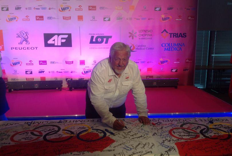 Józef Baściuk, trener Rafała Dobrowolskiego, składa podpis na olimpijskiej fladze (fot. archiwum Józefa Baściuka)