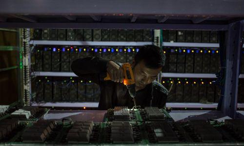 """Syczuan stało się znane jako """"stolica wydobywania bitcoinów"""", ponieważ przedsiębiorczy Chińczycy zakładali tam """"kopalnie"""" właśnie z powodu dostępności do dużych ilości energii wodnej, idealnej przy wysokim zapotrzebowaniu na energię elektryczną wielkich klastrów superkomputerów. """"Kopalnie"""" to budynki o strukturach magazynowych, wyposażonych w ogromną liczbę mikroprocesorów, dzięki którym """"górnicy"""" rozwiązują złożone problemy matematyczne i są nagradzani w walucie cyfrowej. Fot. EPA/LIU XINGZHE/CHINAFILE"""