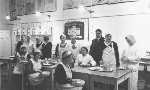 Pojawiła się kuchnia gazowa i pomieszczenie do przygotowywania posiłków w mieszkaniu. Nie ma panien, które skubią gęsi, czasem nie ma w ogóle służby, a pani domu gotuje sama, do tego na gazie i częściej jada na mieście. Na zdjęciu pokaz gotowania zorganizowany przez krakowski oddział Związku Pań Domu w miejskiej gazowni, 1935 rok. Fot. NAC/ IKC, sygn. 1-P-975-2